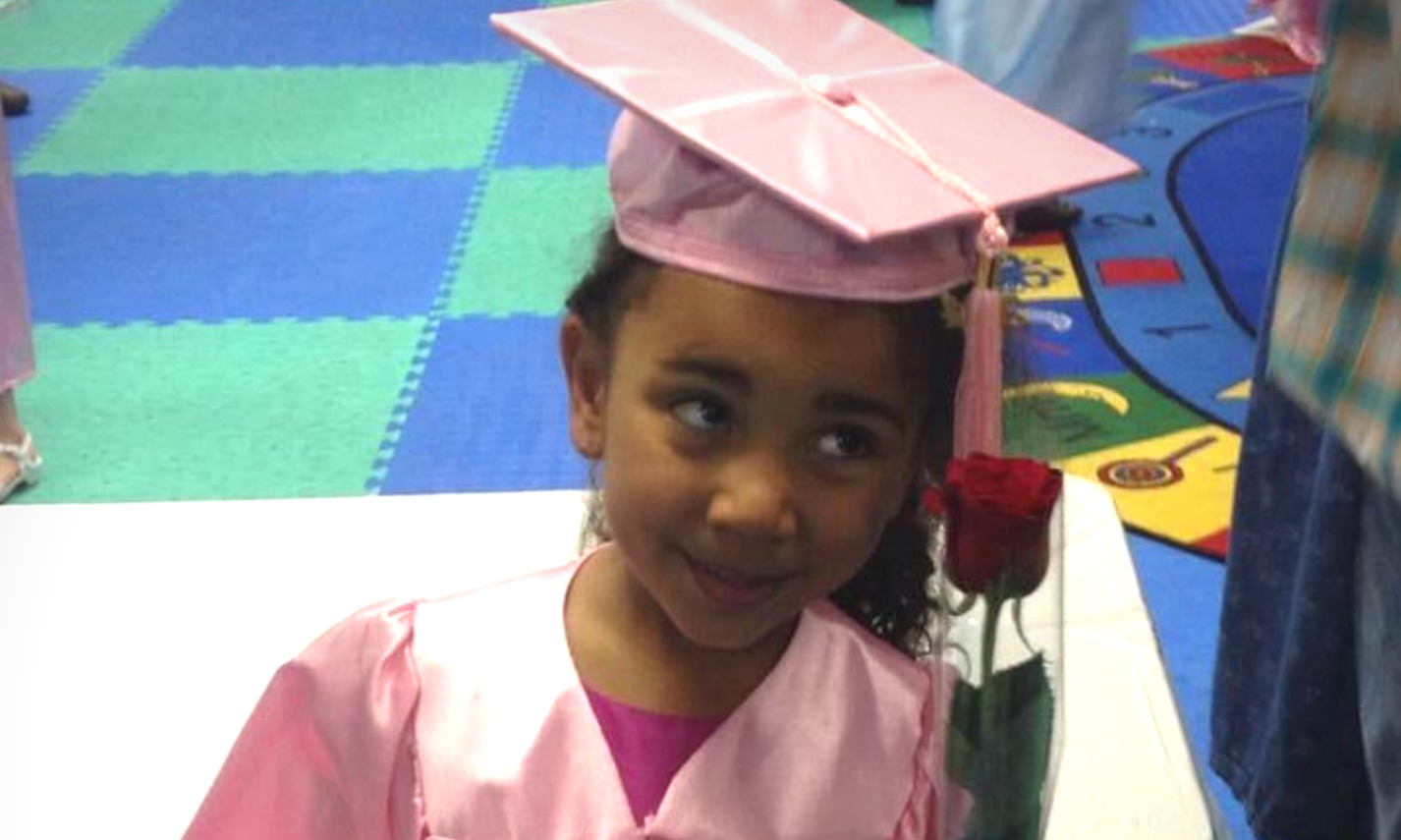 young student in pink graduation cap and gown